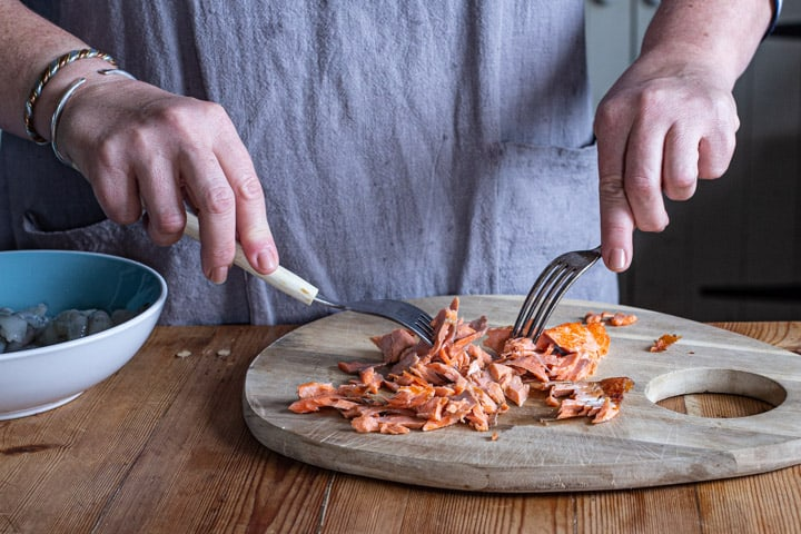 womans hand holding two forks shredding a salmon fillet into flakes