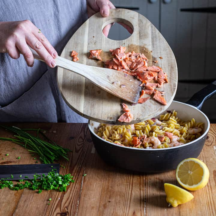 womans hands holding a wooden chopping board of flaked wild salmon over a pan of pasta