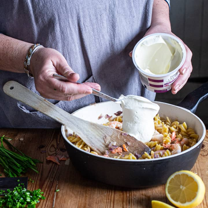 womans hands spooning creme fraiche into a pan of cooked pasta