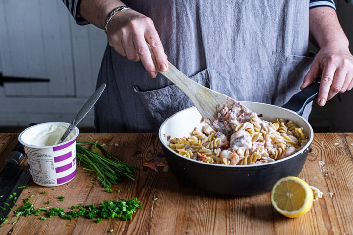 womans hands stirring a pan of salmon and prawn pasta