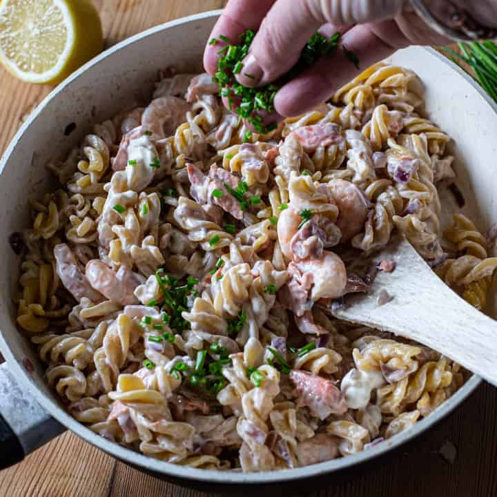 white pan with salmon prawn pasta against a wooden background