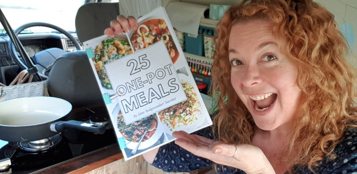 woman in VW campervan kitchen holding a printed A4 ebook called 25 one-pot meals