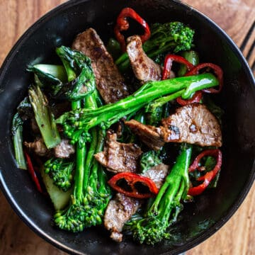 wooden background with black bowl of stir fried broccolini, strips of juicy seared sirloin steak and slices of red chilli