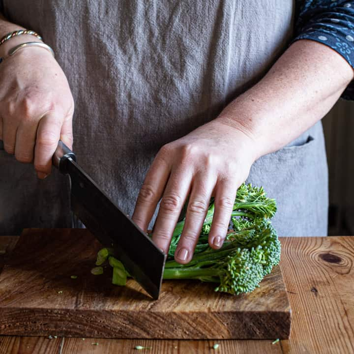womans hands chopping broccoli on a wooden board with large Japanese knife
