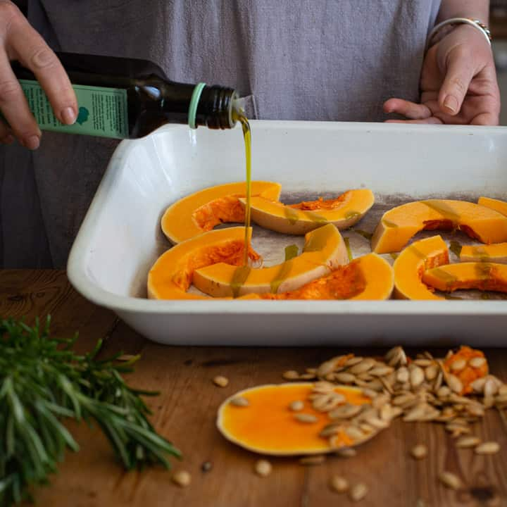 womans hands pouring avocado oil over slices of butternut squash in a white roasting tin