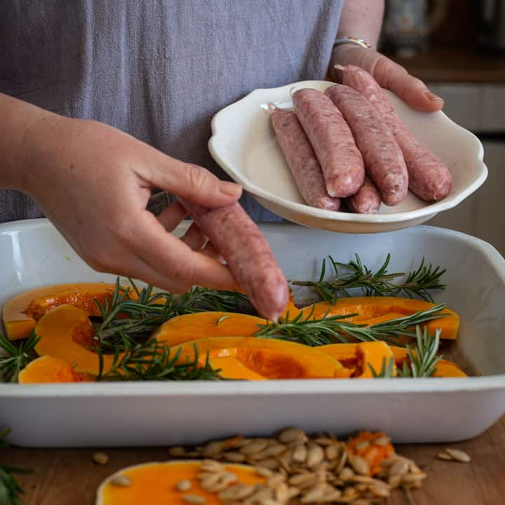 womans hands placing butchers sausages on slices of veggies in a white enamel baking pan