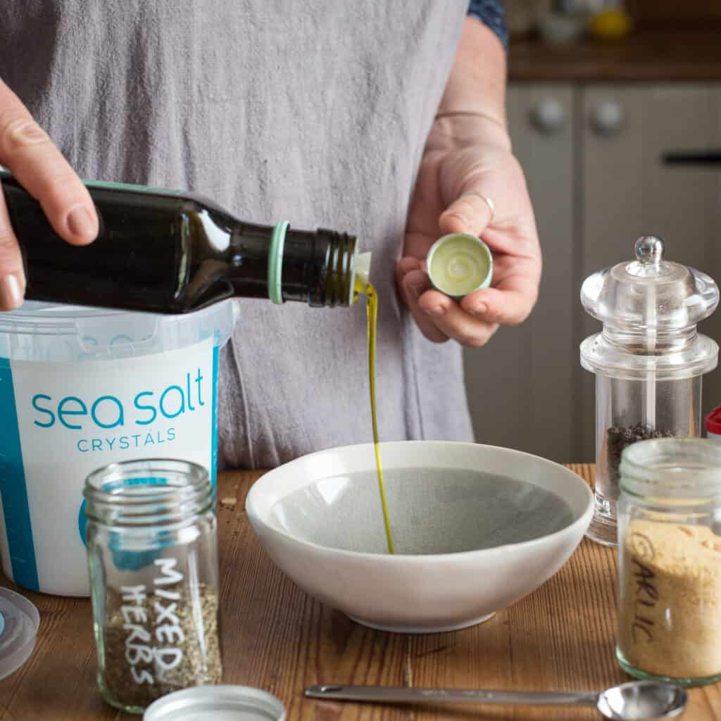 Woman pouring oil from a dark bottle into a smal white and grey bowl on a wooden kitchen counter