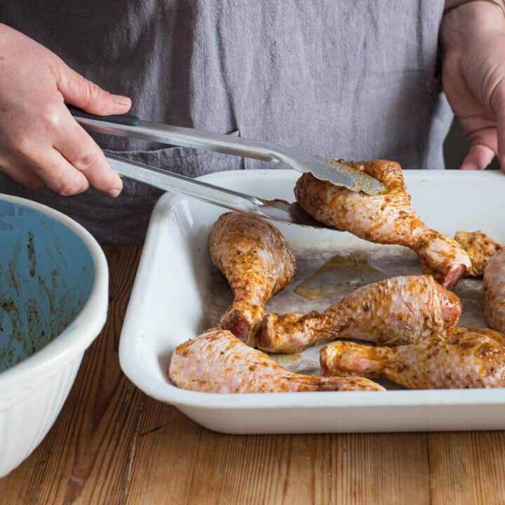 Woman in grey placing marinated chicken drumsticks onto a white enamel baking tray