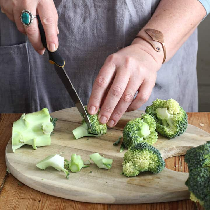 Woman in grey cutting broccoli florets into a tiny pieces for a salad with a sharp knife