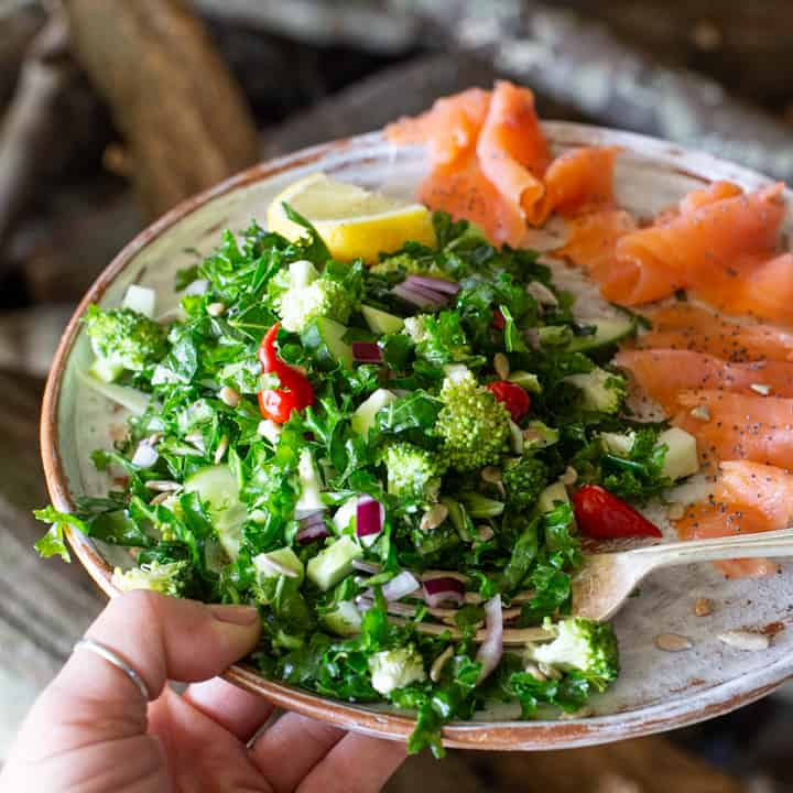 White plate with bright green broccoli kale salad, lemon slice and smoked salmon slices
