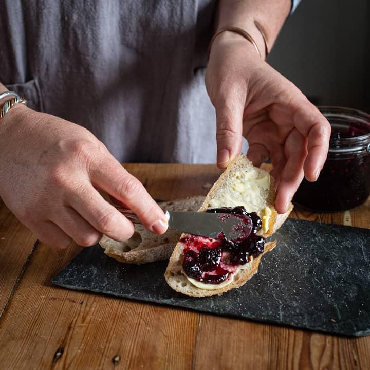 Woman in grey spreading homemade blackberry jam onto aa slice of sourdough bread on a grey slate board