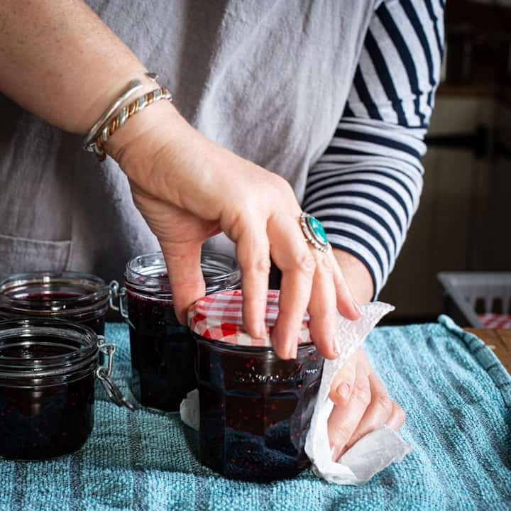 Woman's hands screwing red jar lids onto glass jars filled with hot blackberry jam