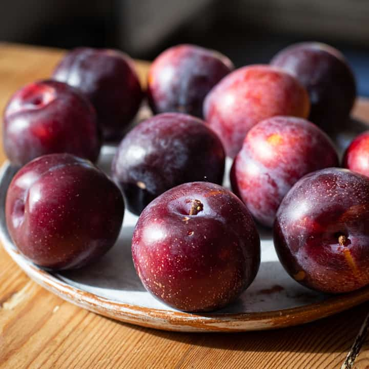 Wooden counter with white plate topped with several fresh red plums