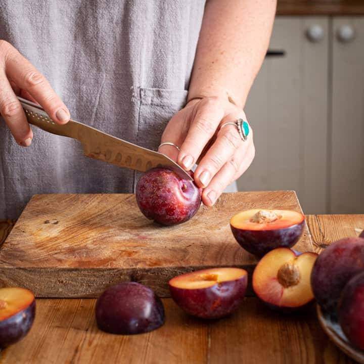 Wooden kitchen counter with a woman in grey slicing red plums in half with a large silver knife