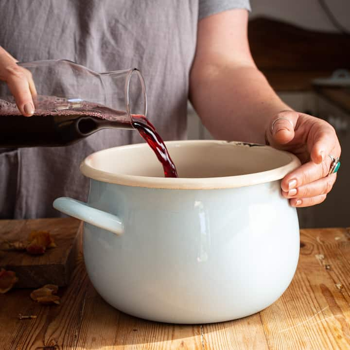 Woman in grey pouring red grape juice from a glass bottle into a blue and white saucepan