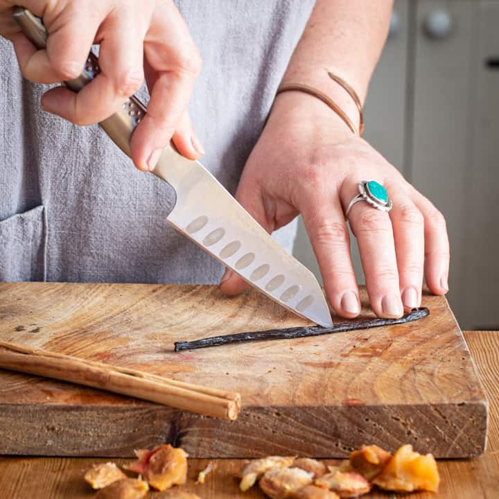 Woman's hands slicing a vanilla pod on a wooden chopping board