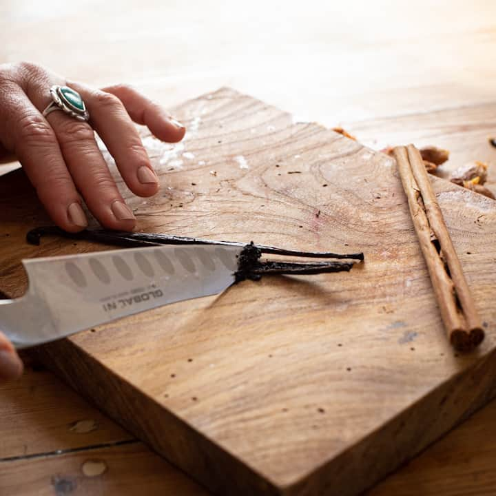 Woman's hands scraping the seeds from a vanilla pod on a wooden chopping board