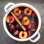 White saucepan on grey slate containing halved red plains in a red grape sauce with a cinnamon stick and vanilla pod