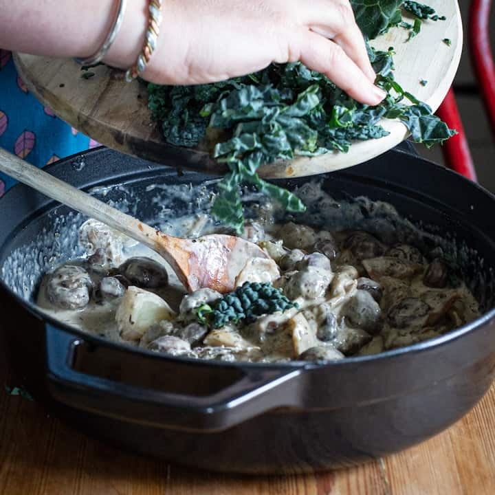Woman's hands tipping chopped kale into a pan of creamy mushrooms