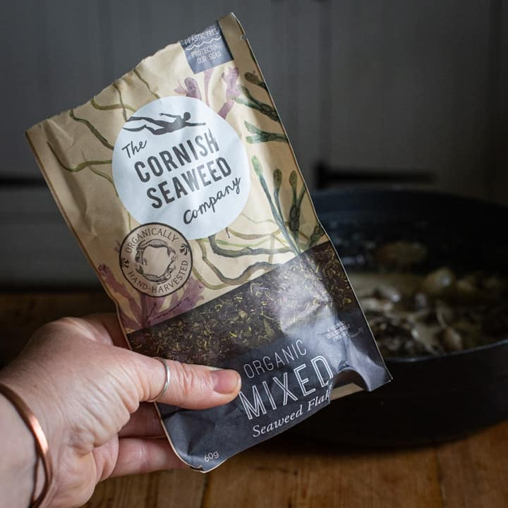 Woman's hand holding a small bag of mixed seaweed flakes by the Cornish Seaweed Co