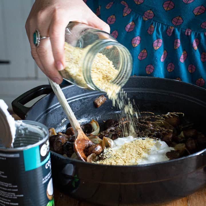 Woman tipping nutritional yeast from a glass jar into a black cast iron pan of vegan stroganoff