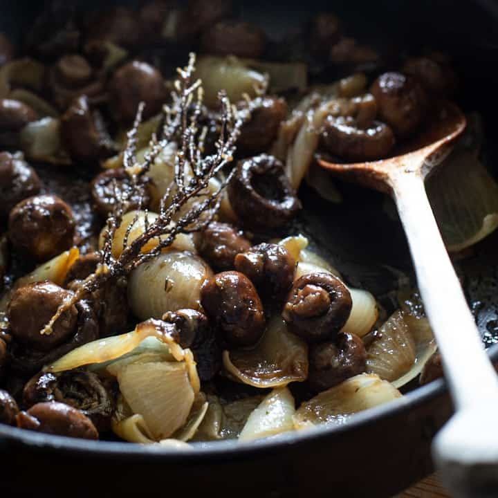 Close up of mushrooms and onions being cooked in a black skillet