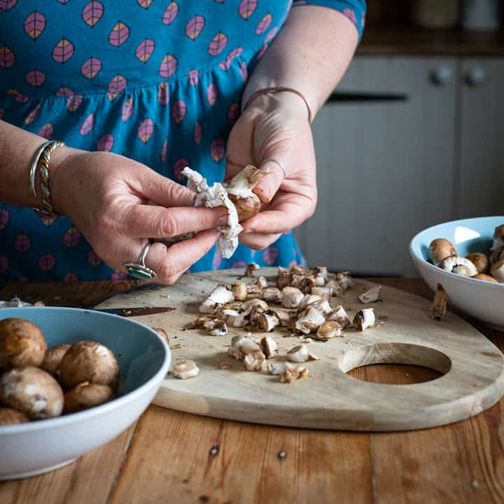 Woman brushing dirt from baby chestnut mushrooms with a piece of white kitchen paper