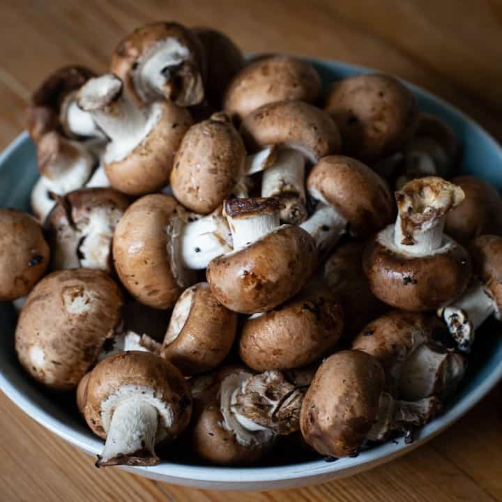 Bowl of baby chestnut mushrooms on a wooden kitchen counter